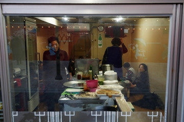 People have dinner in a restaurant near the Jungang Market in Gangneung