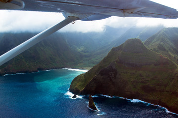 Aerial view of the sea cliffs of Molokai, Hawaii, the highest in the world, with the wing of a small prop plane