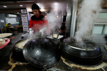 A vendor sells traditional oxtail soup at the Jungang Market in Gangneung