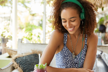 Happy dark skinned mixed race female enjoys pleasant melody in headphones while rests at cafe and waits for her order. African American teenage girl listens favourite music. People and entertainment