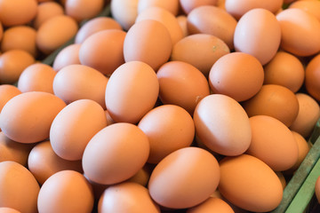 Background photo of pile fresh chicken eggs in the market.