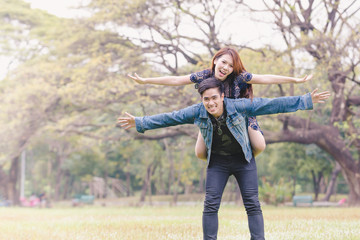 Asian couple lovers under a vast field of nature in a park.