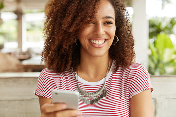 Happy smiling African American female with curly hairstyle sends feedback to interesting video on internet website, uses modern cell phone for chatting with friends duing free time in restaurant