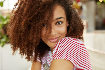 Sideways portrait of stylish female with curly Afro hairstyle and dark skin, being satisfied to achieve great success in life, poses indoor. Close up shot of beautiful African woman has free time