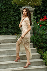 Attractive and elegant rich young lady in dress is posing on stairs of beautiful estate in park. Summer out