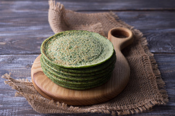 Wooden board with a stack of spinach pancakes on the wooden table, rustic style, selective focus