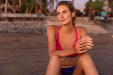 Slender female model in pink top, has pensive expression while sits on sand beach, has workout at open air, prepares for sport competitions. Fitness woman relaxes after active cardio training