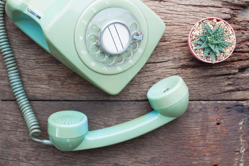 Flat lay vintage style with vintage phone and Cactus plant on wooden table