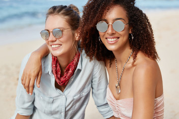 Lesbian couple spend summer vacations at tropical beach, embrace each other and enjoy togetherness. African American female in shades has homosexual relationships with Caucasian blonde woman