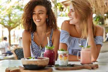 Pleased female lesbians meet together at cafe, enjoy tasty desserts, have recreation at tropical country, discuss something positive. Mixed race women sit against outdoor terrace cafeteria interior