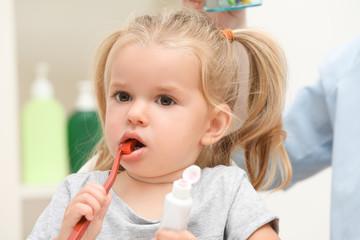 Little girl brushing teeth in bathroom