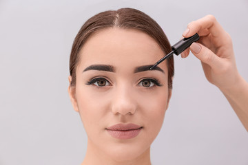 Young woman undergoing eyebrow correction procedure on light background