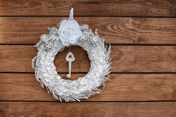 Beautiful Christmas wreath made by professional florist hanging on wooden background