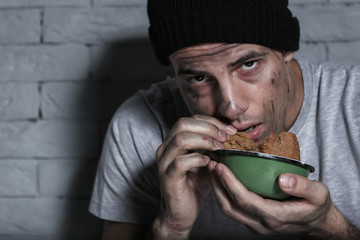 Hungry poor man eating piece of bread near brick wall