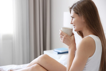 Young beautiful woman drinking coffee on bed at home