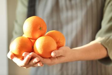 Woman holding juicy ripe oranges, closeup