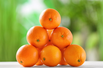 Juicy ripe oranges on table against blurred background