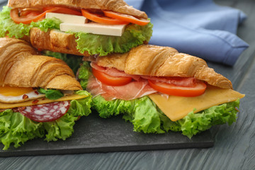 Tasty croissant sandwiches on table