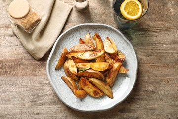 Plate with tasty potato wedges on table