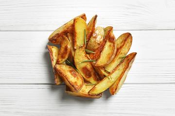 Tasty potato wedges on wooden table