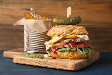 Tasty burger and potatoes on wooden board