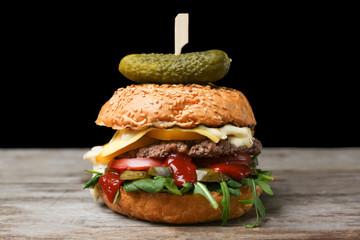Tasty burger on table against dark background
