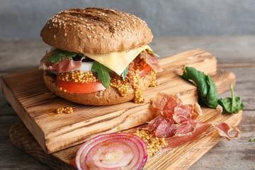 Tasty burger with mustard on wooden boards