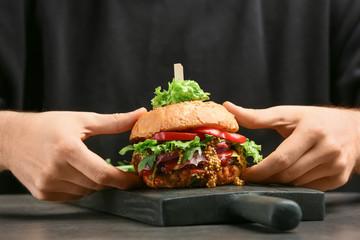 Man holding tasty burger, closeup