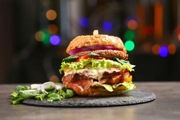 Tasty burger on slate plate against dark background
