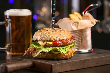 Tasty burger on wooden board against dark background