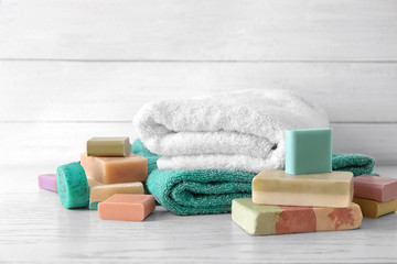 Soft towels and different soap bars on table