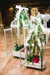 Beautiful large candles stand on the floor, decorated with flowers. Wedding
