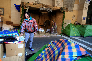Angela Grossi stands next to her tent in the portico of the Basilica of the Santi Apostoli where she lives in Rome