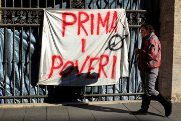 "Angela Grossi walks past a banner reading ""Poor first"", hanging in a gate of the portico of the Basilica of the Santi Apostoli in Rome"