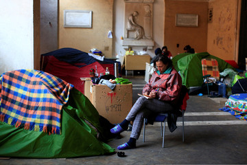 Angela Grossi sits next to her tent in the portico of the Basilica of the Santi Apostoli where she lives in Rome