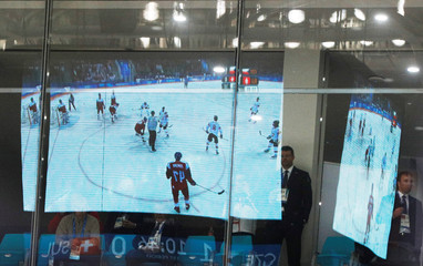 Video of the men's ice hockey game between Switzerland and the Czech Republic is reflected on glass booth overlooking the Gangneung arena at the PyeongChang 2018 Winter Olympics in Gangneung