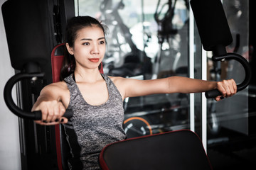 Young Asian woman working out on an exercise machine in the modern gym