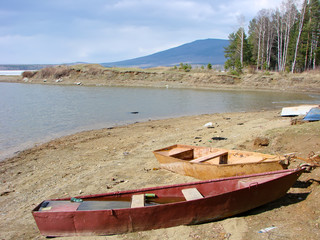 Boats on the bank of the Nizhnevoy reservoir, against the background of the Kachkanar mountain. Kachkanar. Sverdlovsk region. Russia