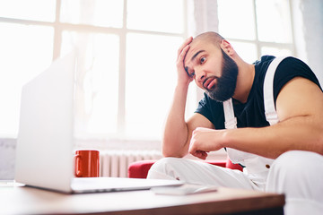 Stressed and tired young man with beard working on laptop computer at home.