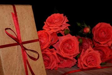 красивый подарок перевязанный красной лентой с красивыми розовыми розами