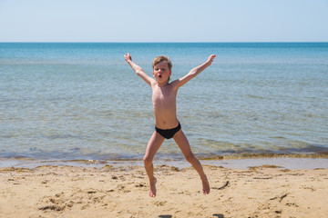 Six-year-old boy in black speedo jumping into the sea and shouts.