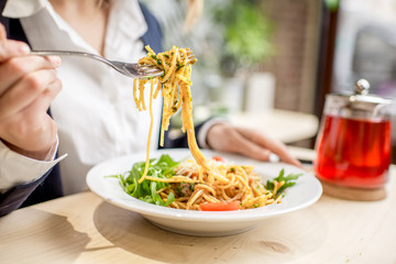 Businesswoman having lunch with pasta and fruit tea at the restaurant. Close-up view on the pasta