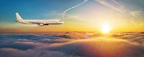 Airplane jetliner flying above clouds in beautiful sunset light.