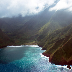 Aerial view of the coastline and foggy sea cliffs of Molokai, Hawaii, shot from a small, low-flying prop plane