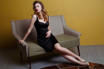 A chic young girl in a tight black dress sits on the couch.