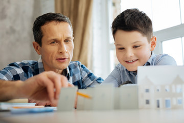 Useful information. Pleasant young man pointing at the models of solar panels standing on his table while telling his son about their benefits