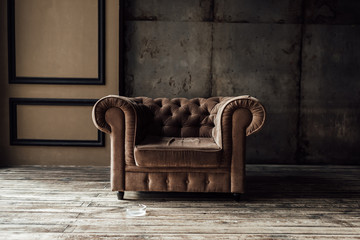 Fototapeta luxurious brown armchair and ashtray on floor in loft interior obraz