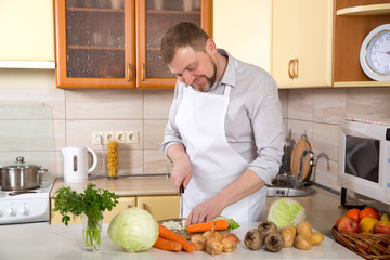 Man in the kitchen is preparing a salad of fresh vegetables. Vegetarian menu.