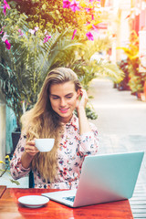 Beautiful woman is working on laptop and enjoying a cup of cofee in the cafe
