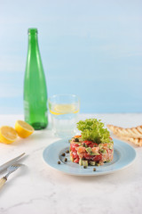 Tar-tar from salmon with avocado and tomatoes on a blue plate. Next to the plate are cutlery and toast. In the background, a lemon, a glass of water and a bottle. Light background. Vertical shot.